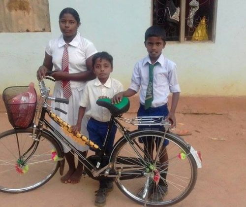 Vision of Love donates a bicycle to a schoolgirl